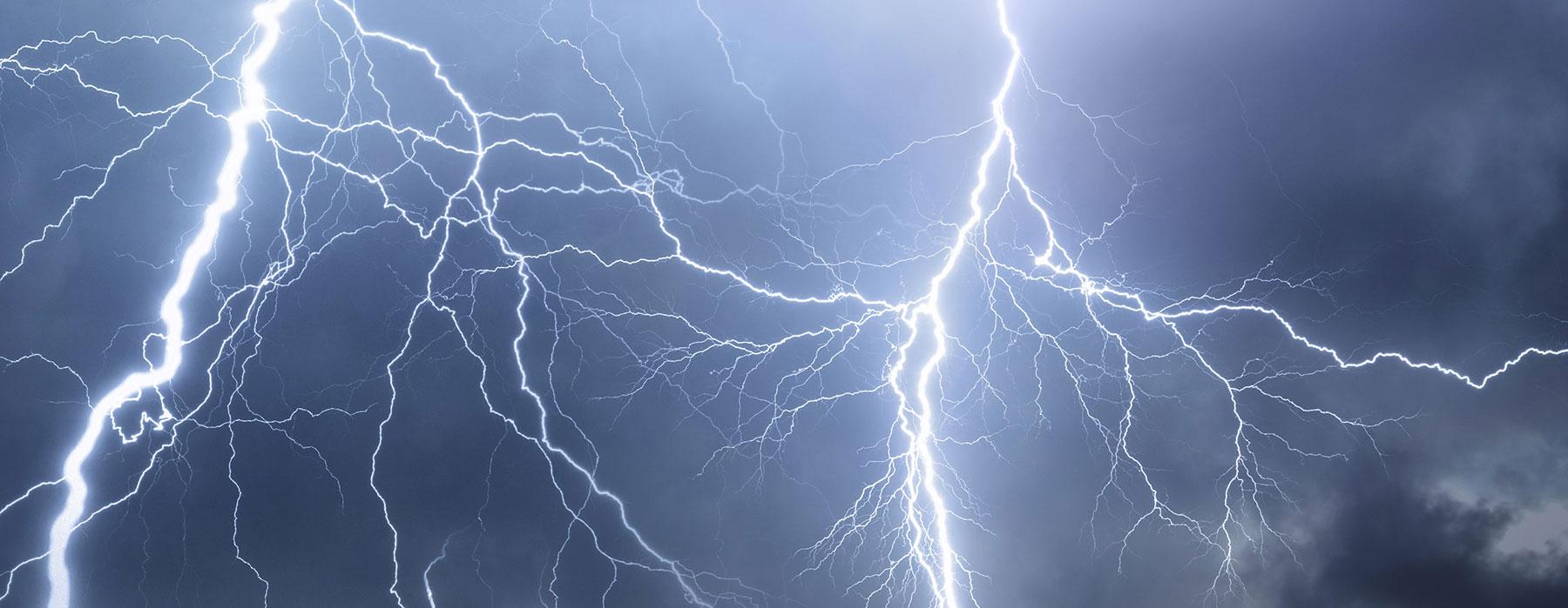 Der Himmel ist von Blitzen durchzogen, vor denen Häuser geschützt werden sollen.